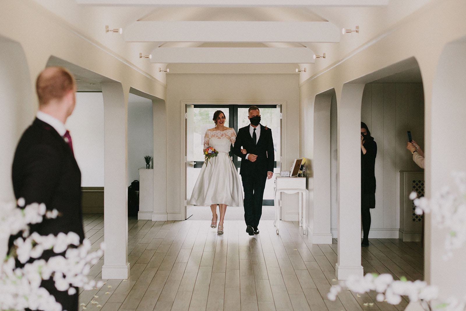Newly married Bride and Groom walking in the entrance of the main wedding room at All Saints Hotel