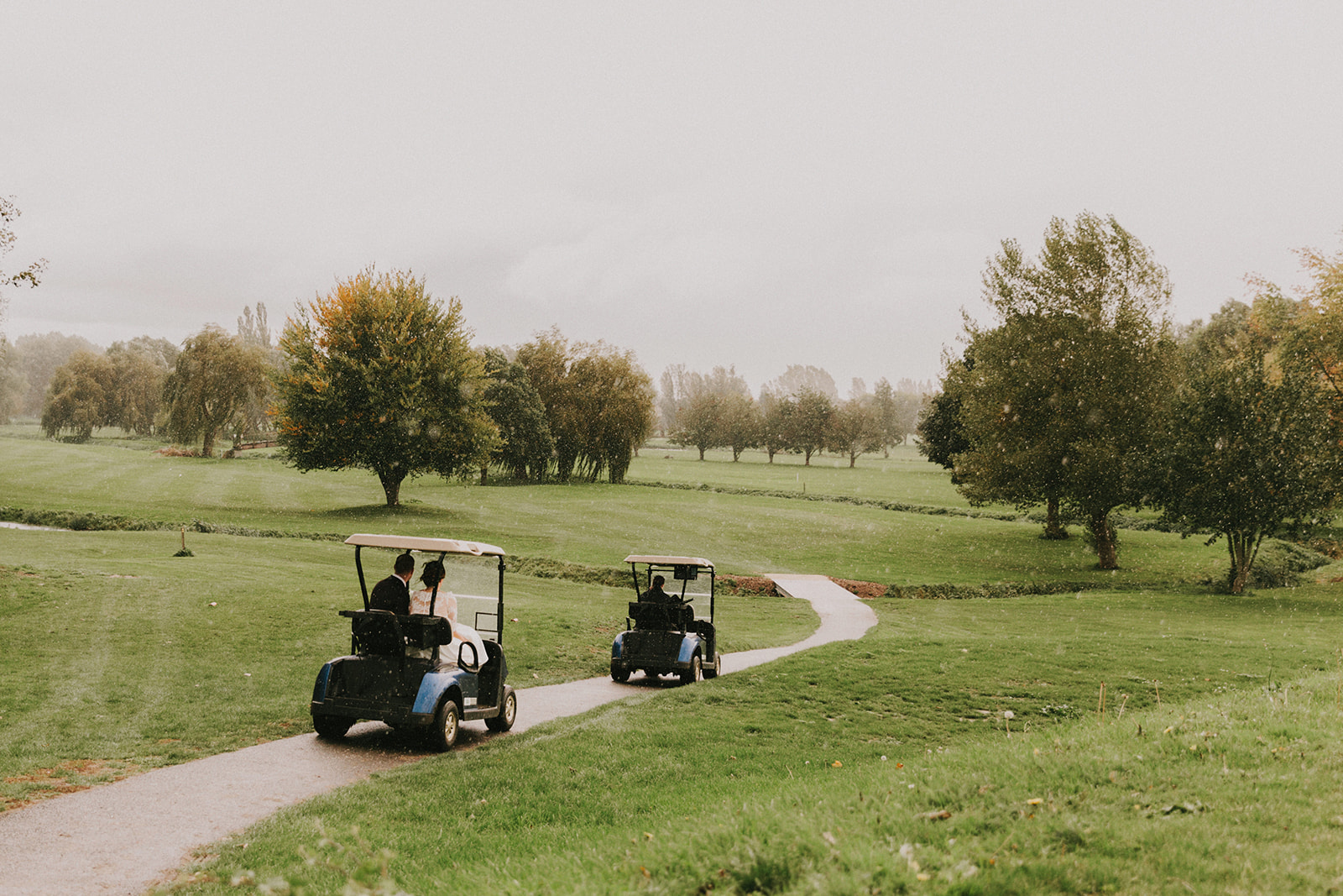 Newly married couple in Golf carts driving through The Suffolk Golf Course at All Saints Hotel