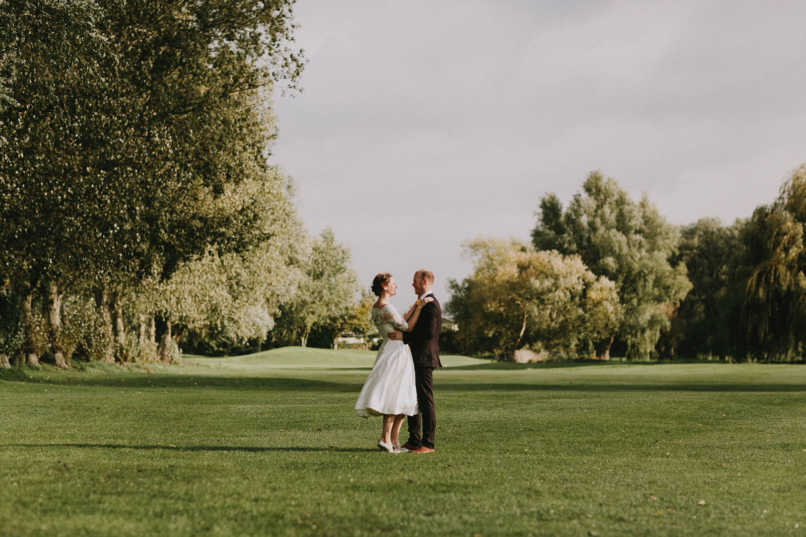 Newly married couple embracing on a fairway in the grounds of The Suffolk Golf Course at All Saints Hotel
