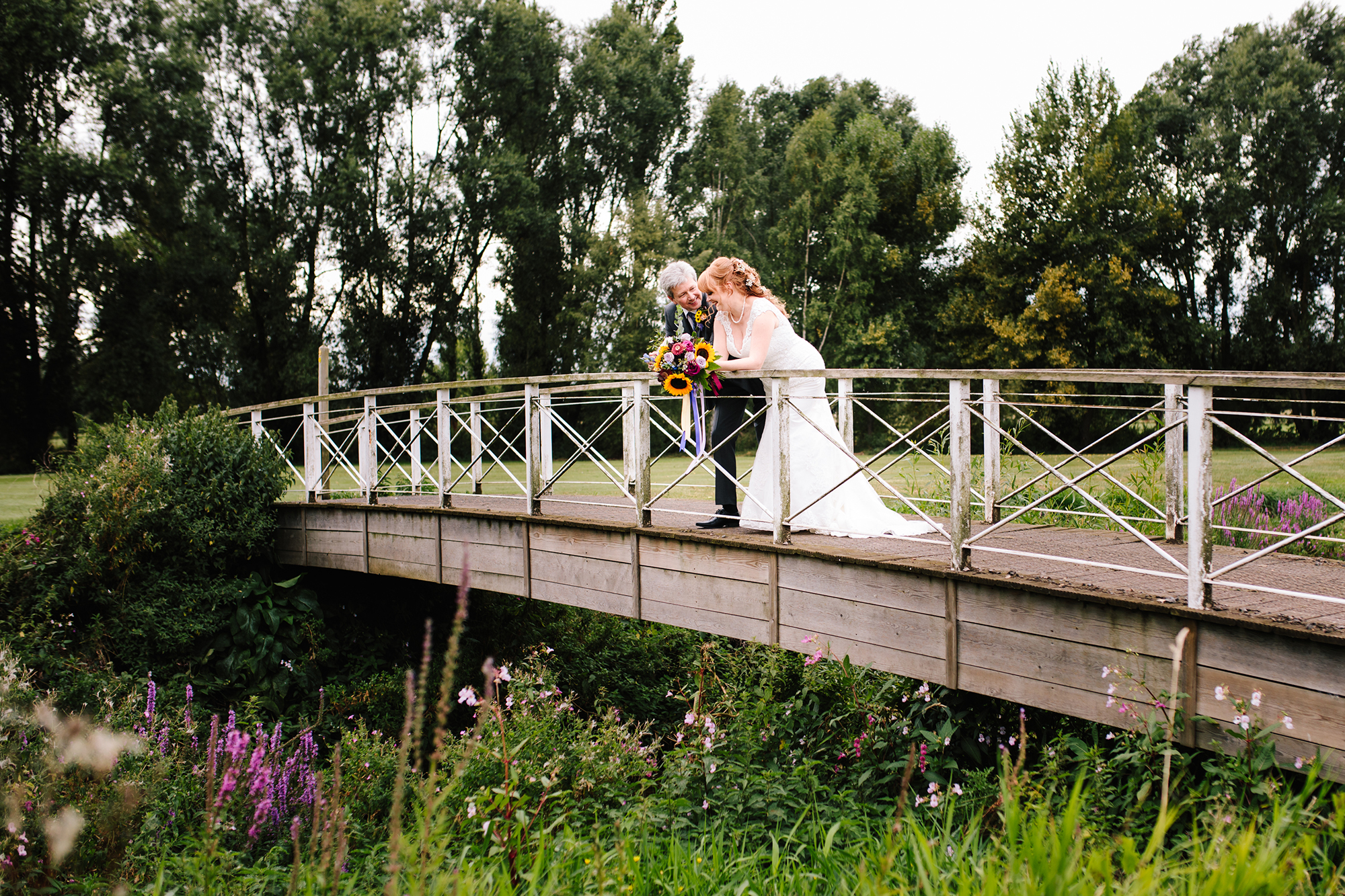 Newly married couple chatting on a bridge in the grounds of The Suffolk Golf Course at All Saints Hotel