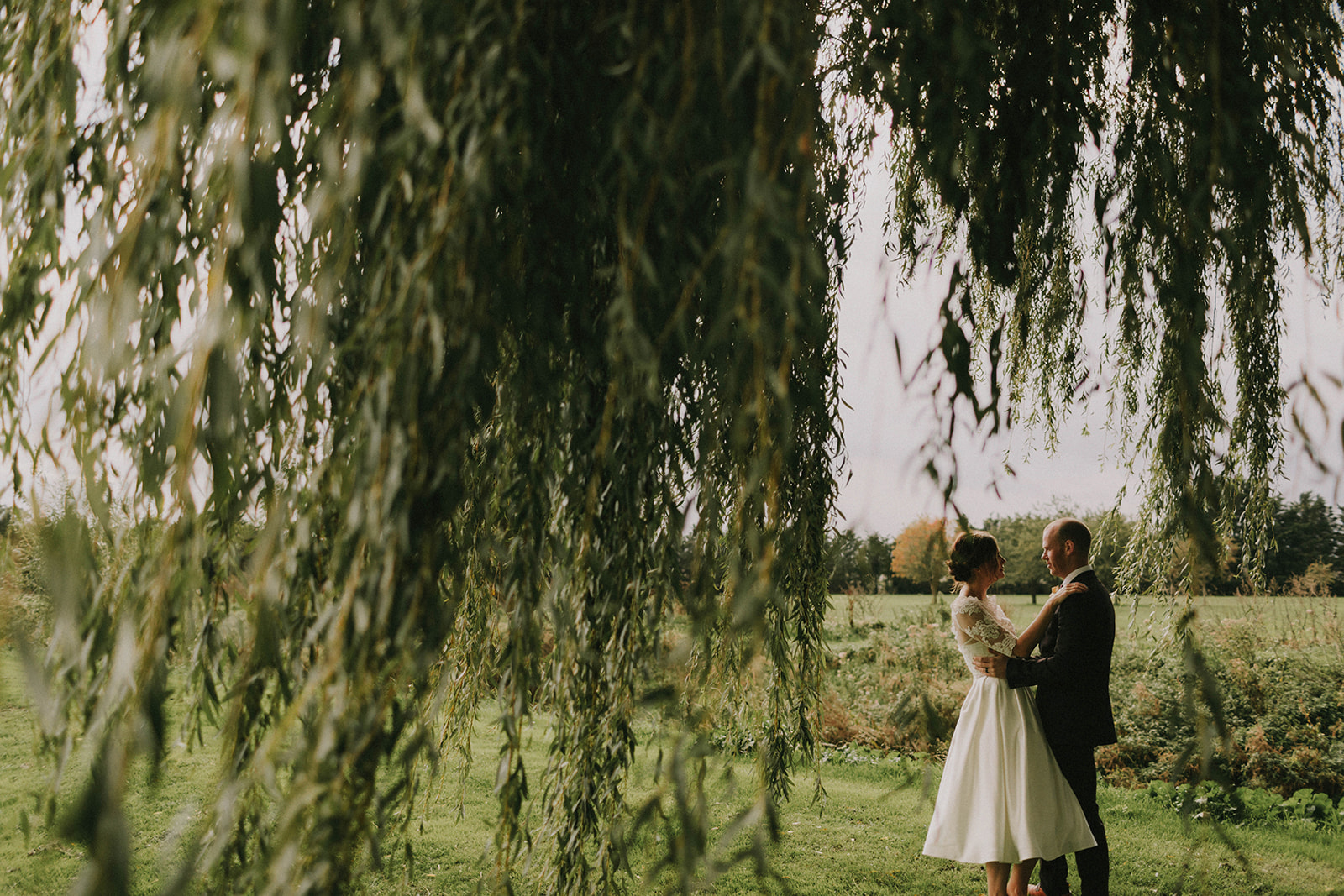 Newly married couple embracing under a willow tree in the stunning gardens at All Saints Hotel