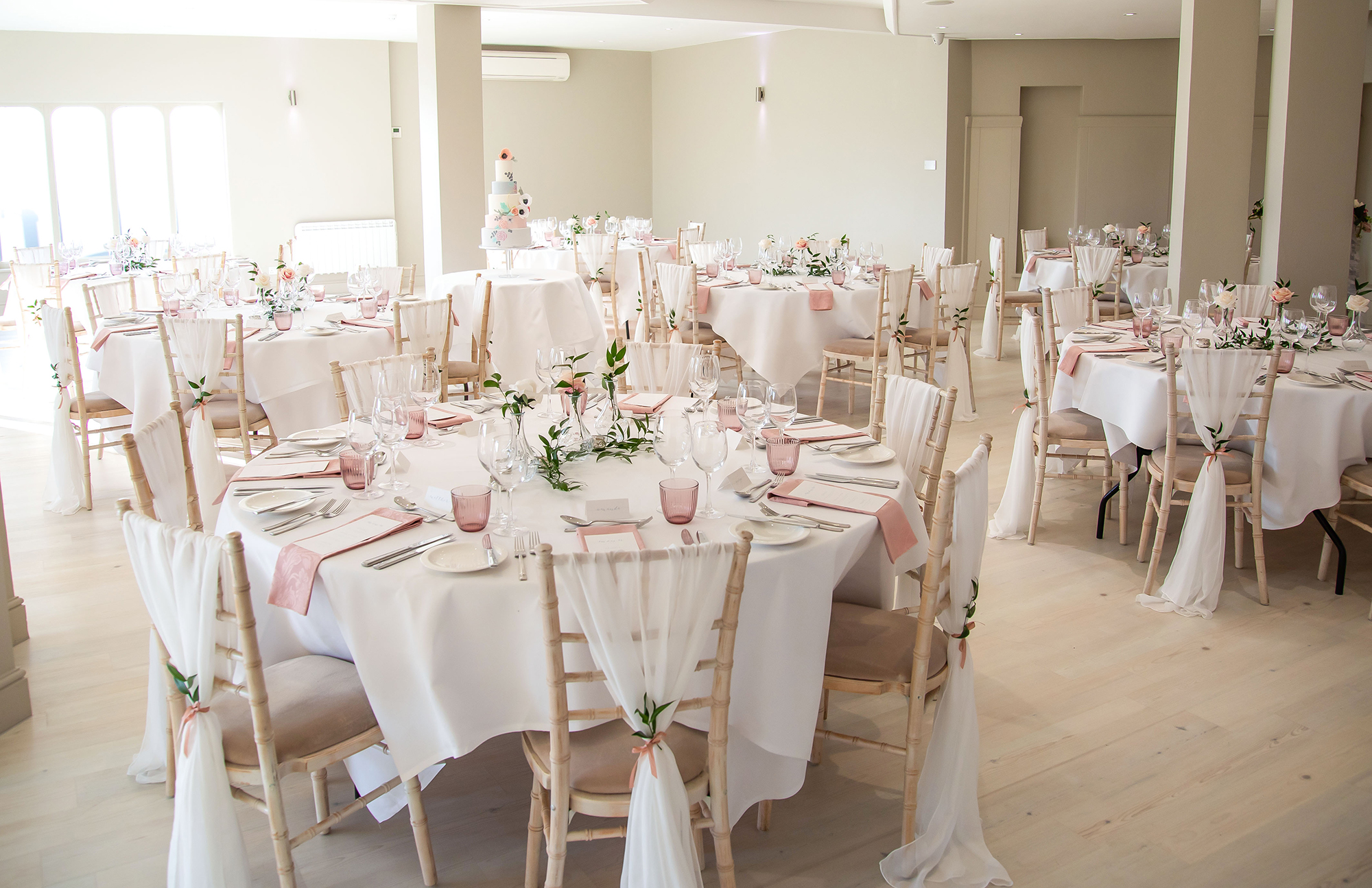 Stunning laid tables with a pink and white theme ready for the wedding breakfast, in the main function room at All Saints Hotel