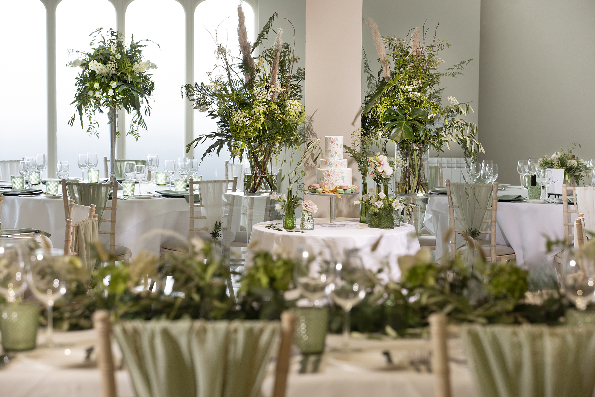 Stunning laid tables with flowers ready for the wedding breakfast, in the main function room at All Saints Hotel
