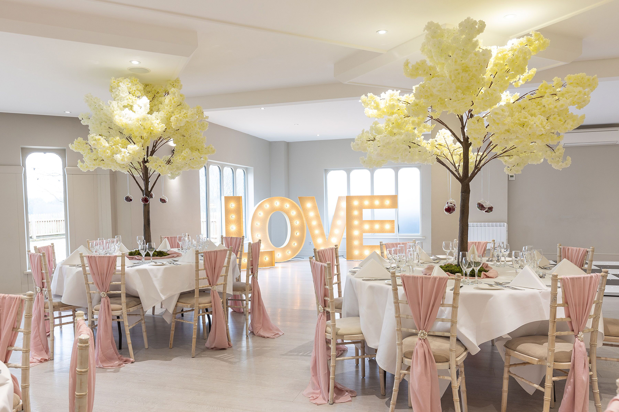 Beautiful laid tables and trees with a yellow, pink and white theme ready for the wedding breakfast, in the main function room at All Saints Hotel