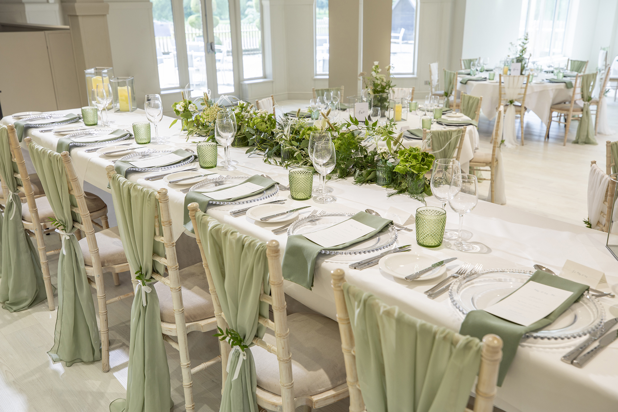 Beautiful laid tables and flowers with a green and white theme ready for the wedding breakfast, in the main function room at All Saints Hotel