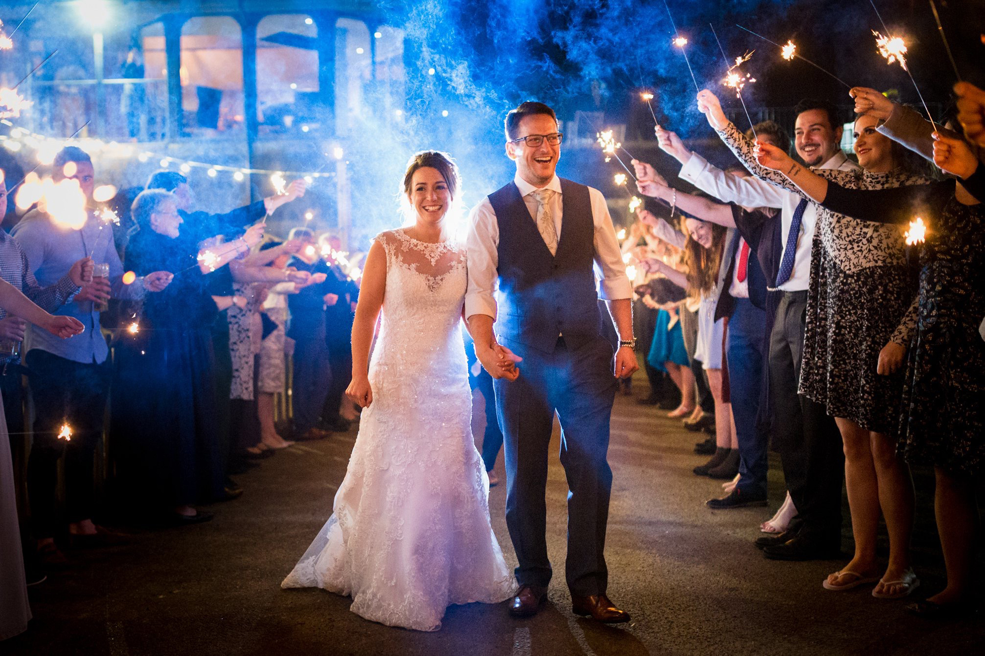 A newly married couple walking down a procession of celebrating friends and family holding sparklers at All Saints Hotel