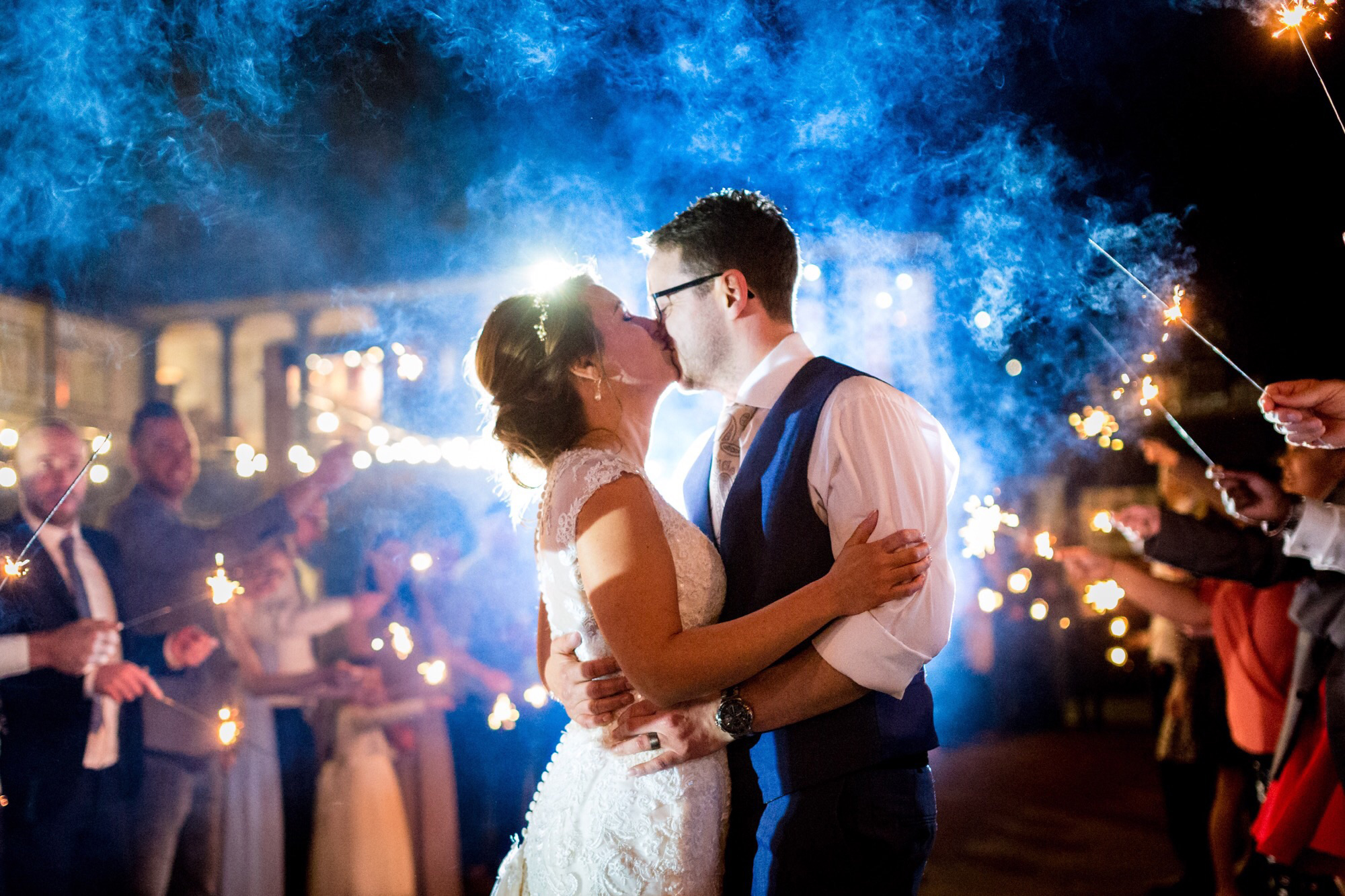 A newly married couple kissing outside All Saints Hotel, in the evening with the congregation holding sparklers and celebrating